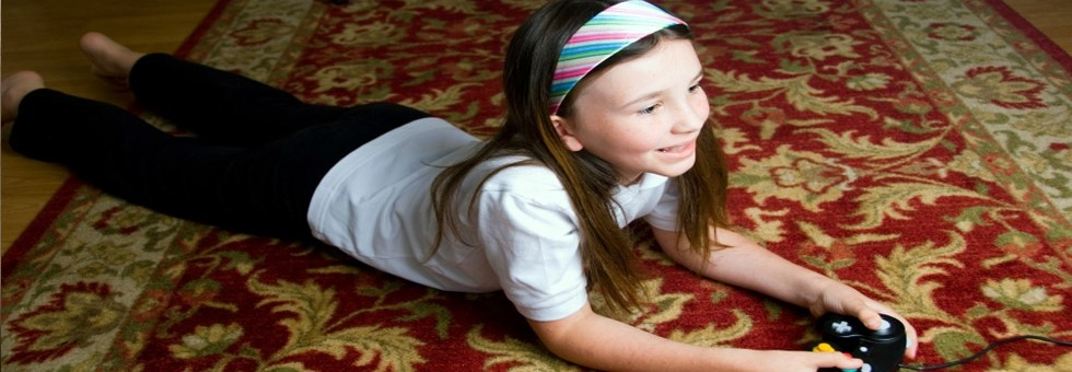 Girl laying on a carpet playing video games