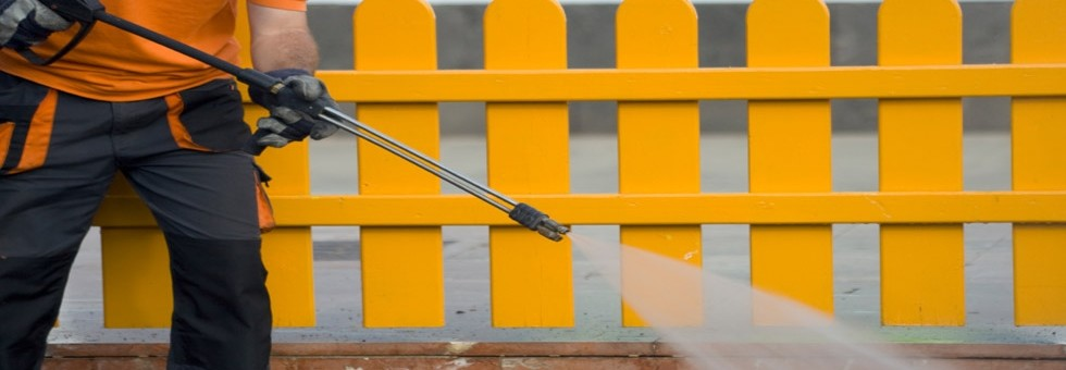 Man power washing near a yellow fence