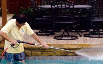 a professional power washing a swimming pool in north texas