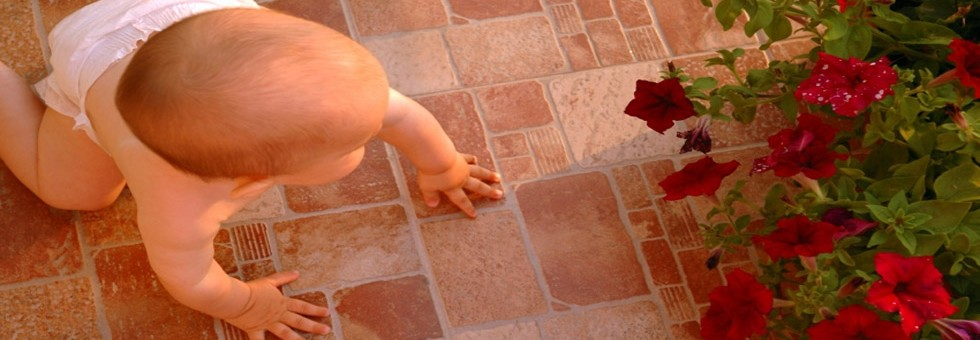 Baby crawling on clean tile and grout