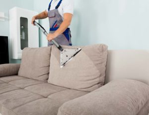 Upholstered couch being cleaned
