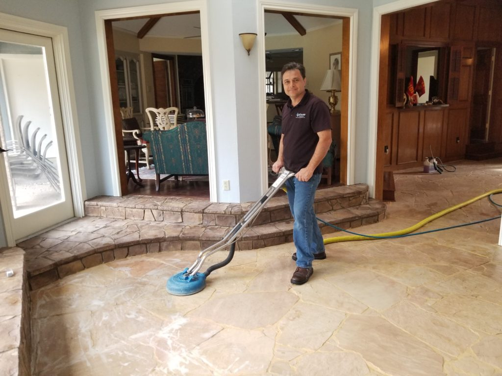 Frank Listorti cleans a stone floor at a home in Dallas