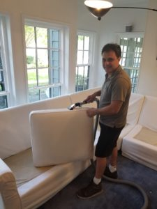 a man cleaning a couch in a home in dallas texas