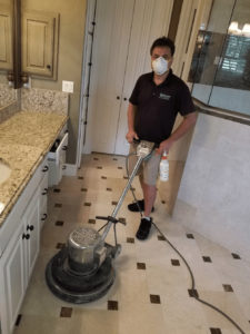 a man wearing a mask while polishing a marble bathroom in Plano Texas
